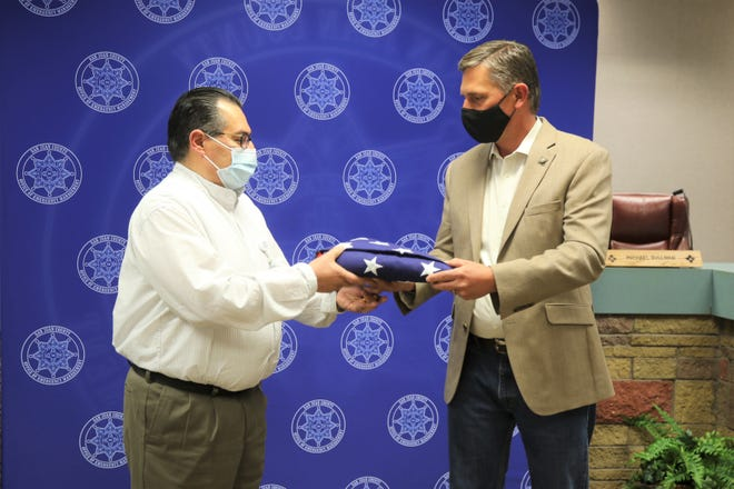 San Juan County Emergency Manager Mike Mestas, left, receives an American flag flown over the U.S. Capitol from Senator Martin Heinrich (D-N.M.), right, at the San Juan County Administrative Building in Aztec. Mestas was recognized as a Hometown Hero for his work confront the COVID-19 pandemic by Heinrich.