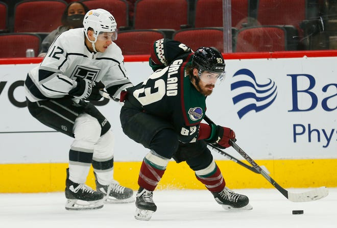 May 3, 2021; Glendale, Arizona, USA; Coyotes' Conor Garland (83) skates with the puck against Kings' Trevor Moore (12) at Gila River Arena. Patrick Breen-Arizona Republic