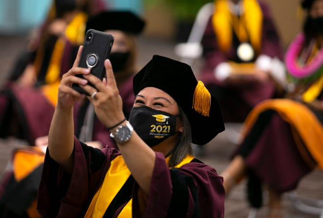 ASU nursing student Diane Rodriguez Villayuran takes a selfie before the start of the graduation ceremony for ASU's Edson College of Nursing and Health Innovation in Phoenix on May 3, 2021.