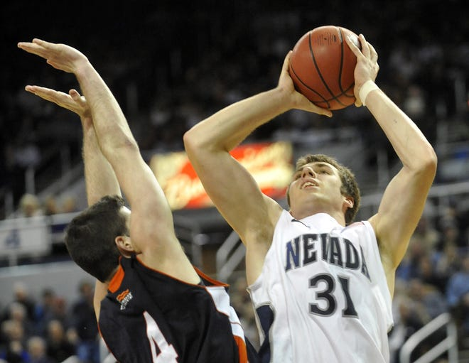 Nevada forward Olek Czyz goes up for a shot as Bucknell's Bryan Cohen defends during the final minutes of their game at Lawlor Events Center on March 18, 2012.
