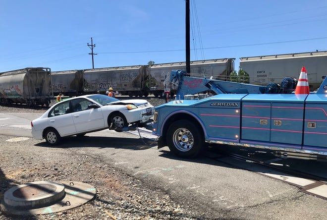A white sedan was towed away after a reported collision with a train in south Redding on Tuesday, May 4, 2021.