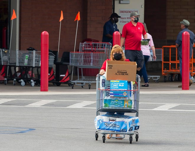 Masked shoppers exit Costco and load their groceries into their vehicles Tuesday, May 4, 2021.
