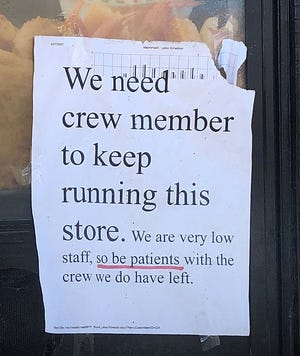 A sign on a local restaurant drive-thru illustrates the difficulty businesses are having recruiting workers.