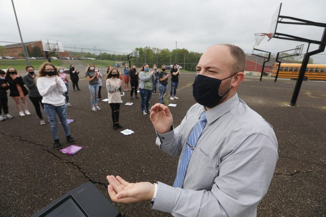 Maysville High School choir director Ryan Hutcherson directs students during an outdoor practice on Tuesday.