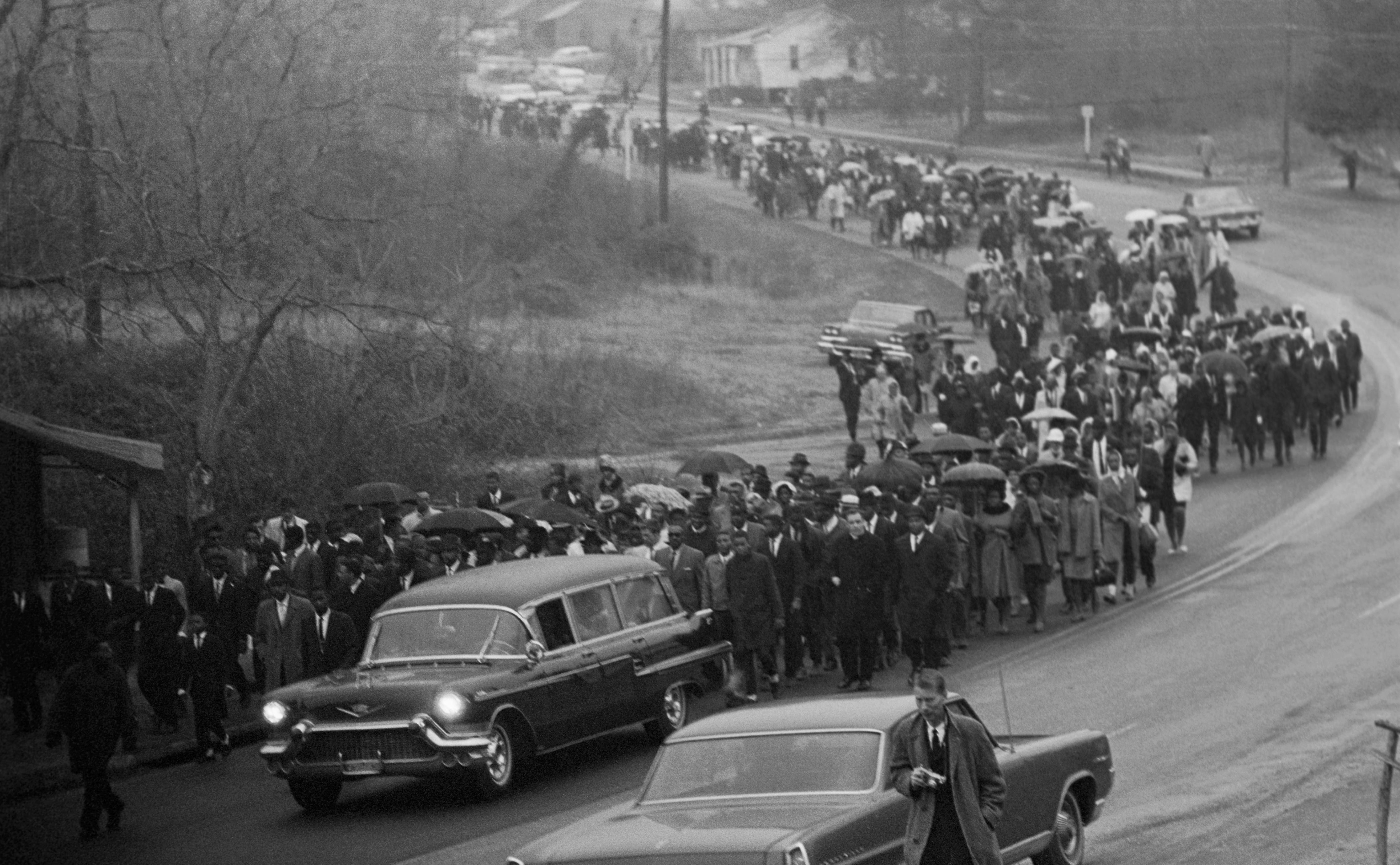 A hearse carrying the body of Jimmie Lee Jackson drives slowly in rain with an estimated 700 people, mostly African American, following the cemetery where Jackson is to be lain. Jackson was shot in Marion February 18, during a night demonstration and died in Selma Hospital. Two funerals were held for the civil rights protester with Dr. Martin Luther King giving the eulogy.