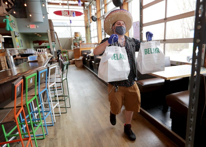 Thaniel Gravelle, a BelAir Cantina front of house manager dons a sombrero as he carries orders to go at the BelAir Cantina on North Water Street in Milwaukee on May 5, 2020.