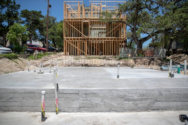 Construction crews work on new townhomes on West Alpine Road in Austin in May.
