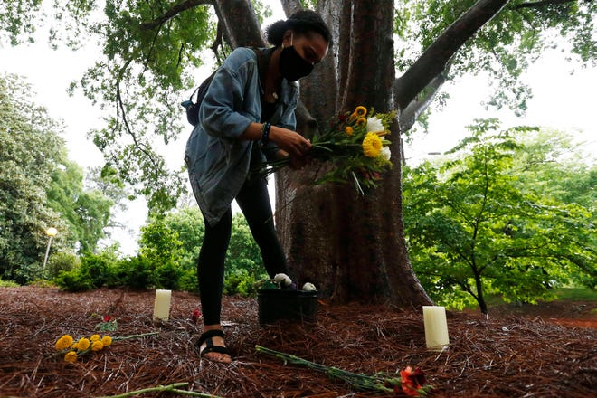 Denise Sunta lays flowers on the ground before the start of the Athens Day of Jubilee celebration and vigil at Baldwin Hall on the campus of UGAin Athens, Ga., on Tuesday, May 4, 2021.