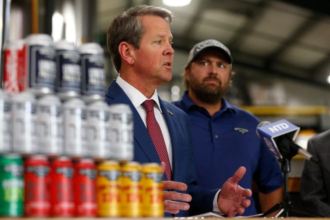 Georgia Gov. Brian Kemp speaks alongside Southern Brewing Company co-owner Rick Goddard before signing Senate Bill 236 and House Bill 273 at SBC in Athens, Ga., on Wednesday, May 5, 2021. S.B. 236 will allow for the restaurants to sell up to two mixed drinks for carryout to patrons and H.B. 273 will allow distillers to sell spirits on the distillery grounds and allow breweries to make retail sales on Sundays.