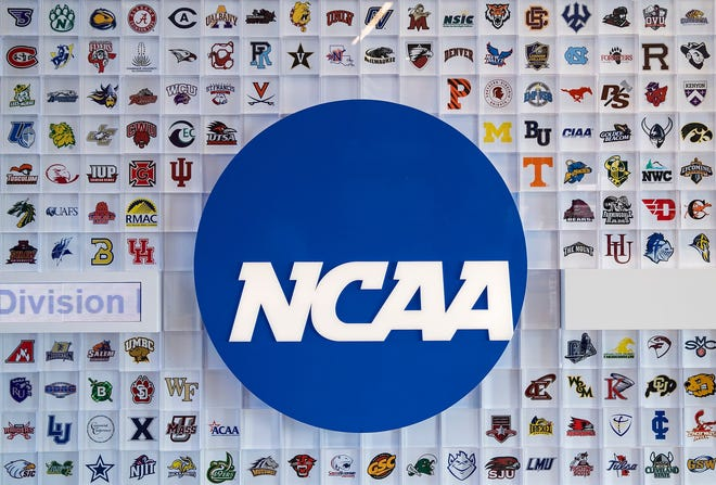 University logos cover a wall in the lobby of the NCAA headquarters Thursday, Feb. 25, 2021, in Indianapolis.
