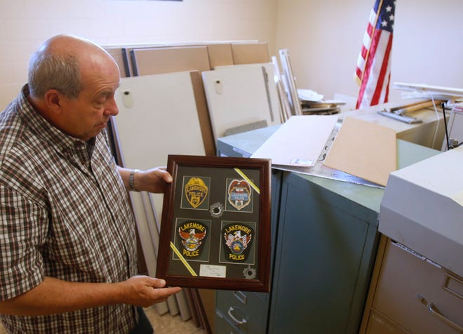 Lakemore Police Chief Ken Ray holds a framed collection of the department's police badges through the years. Ray is retiring May 14.