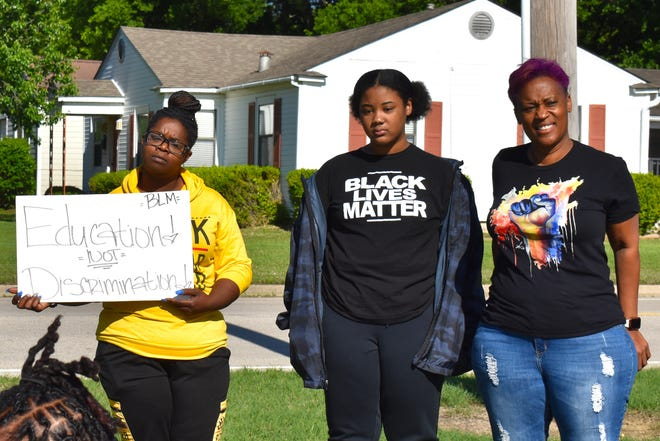 """Black Lives Matter supporters stand in front of an Ardmore elementary school Wednesday, May 5, 2021, to protest school actions against students wearing BLM shirts. The Ardmore City Schools Board of Education last week approved changes to the elementary school dress code that prohibit clothing with """"social or political content."""""""