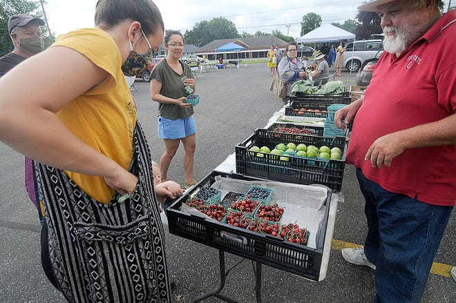 Kaitlynn Dolezal purchases berries at the farmers' market at Christ United Methodist Church on Saturday, June 27, 2020. This farmers' market has been going strong in 2021, too, taking place every Saturday this summer from 9 to 11 a.m. It will wrap up on Oct. 16.