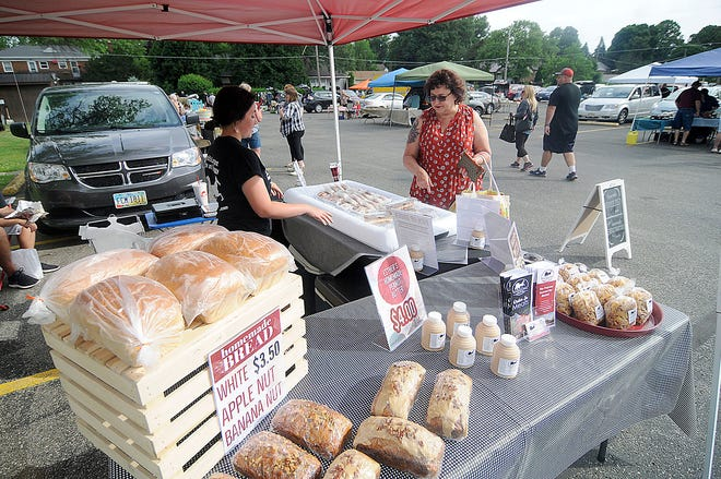 Maddie Shonkwiler helps customer Cheryl Smith with her purchase at the Beyond Measure Market's tent at the farmers' market at Christ United Methodist Church last June.