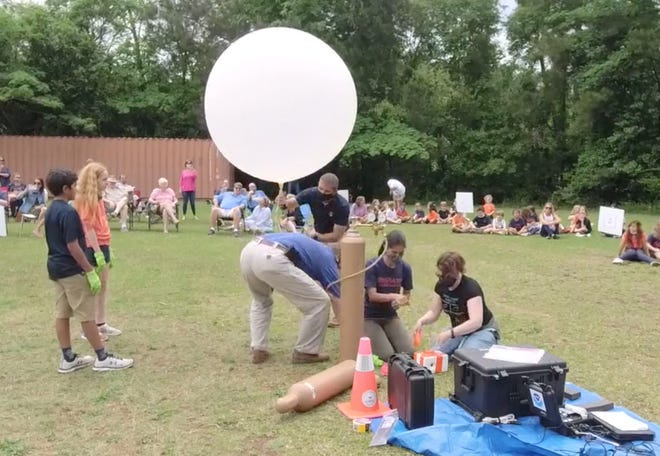 The Amateur Radio Club of Columbia County assists students of Savannah River Academy in Grovetown in prepping a weather balloon to launch Wednesday.