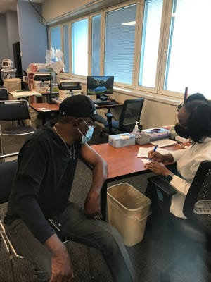 Veteran Michael Harrison, 61, talks with Registered Nurse  Crystal Glover as he receives his second COVID-19 shot at the Charlie Norwood VA Medical Center in Augusta.