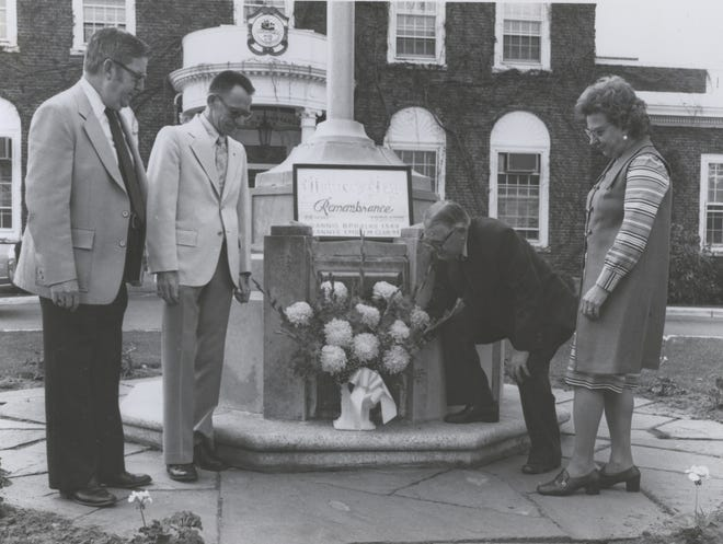 In honor of Mother's Day in 1978, Elmer A. E. Richards, past exalted ruler of Hyannis Lodge of Elks, places flowers at the old Town Hall building accompanied by Barnstable Selectmen Paul Brown, Edwin Taylor, and Mary Montagna.