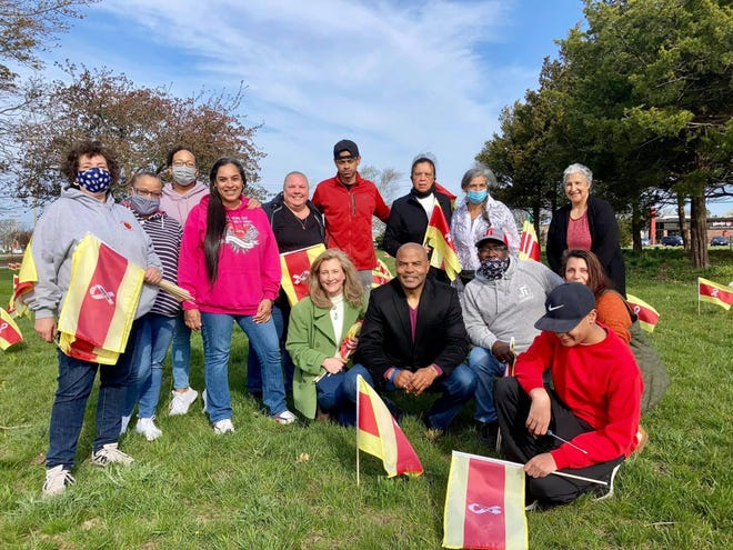 Denise Harris (fourth from left) and friends, including Rep. Kip Diggs (center) plant commemorative COVID-19 flags -- one for each Cape Codder who died of COVID-19 -- at the Hyannis airport rotary last Sunday.