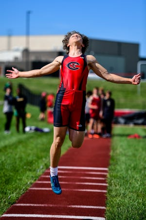 """Junior Braxten Johnson of Chillicothe High School """"climbs"""" through the air to get addition distance on a long jump attempt during Tuesday's Midland Empire Conference Championships track-and-field meet in Chillicothe. Johnson took second in the event and won both hurdles races to apparently be the top points scorer in the boys' division."""