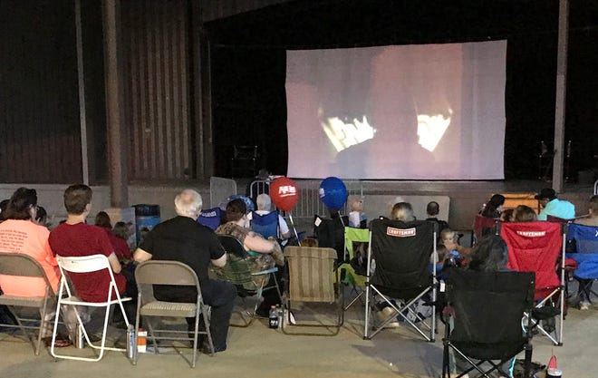 Residents watch a previous Family Movie Night film in the Spanish Trail Park amphitheatre. Families may watch from their chairs or blankets.