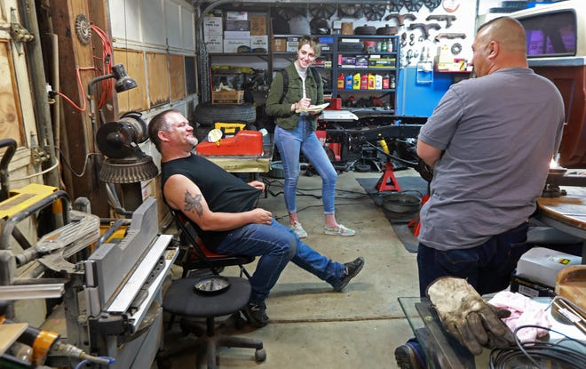 Columbus Dispatch reporter Ceili Doyle talks with Jess Cline (left) and Archie Spradlin inside Cline's Scioto County garage. Doyle was working on a story about people such as Spradlin who claim two distinct heritages: His mother is from Thailand and his father is from Appalachia.