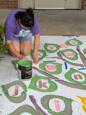 A volunteer helps paint stencils for exercise activities around Terrebonne and Lafourche with the LSU AgCenter Live Healthy Communities initiative.