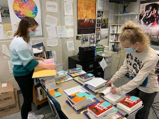 Kiley Young (left) and Sophie Gamble place donation stickers into books that were purchased to be delivered to schools in the tri-county area.