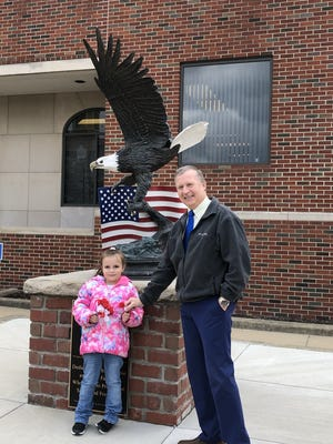 """Evelyn """"Evy"""" Massoni, 7,Orrville's Poppy Girl, presents MayorDave Handwerk with poppies for the in honor of Memorial Day."""