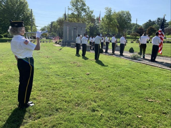 Kathy Bittinger, a member of the Wooster American Legion Post 68 Auxiliary, played taps during the 2020 Memorial Day service at Wooster Cemetery. The ceremony was limited to the American Legion members delivering the rifle salute.