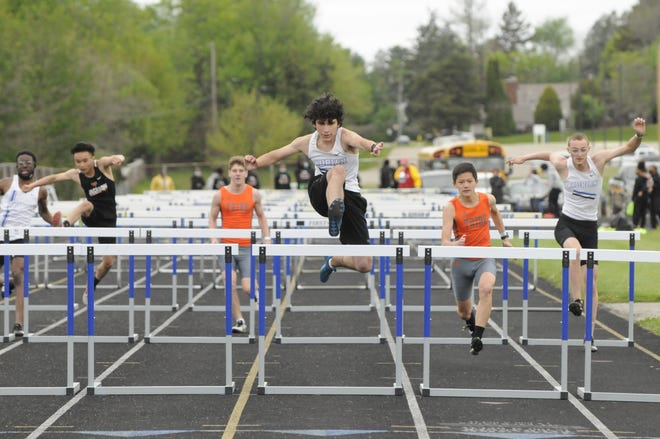 Adrian's Maximus Perez, center, clears the final hurdle during the boys 110-meter hurdle event at Tuesday's SEC White tri-meet against Jackson and Hudson. Perez swept the hurdle events to help the Maple boys win over both Jackson and Tecumseh.