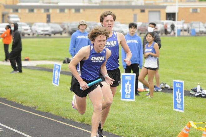 Adrian's Jake Eagling, foreground, takes the baton from Aiden Smith during the 4x800-meter relay event at Tuesday afternoon's SEC White meet against Jackson and Tecumseh.
