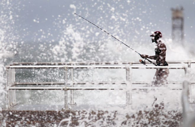 A fisherman on the jetty weathers high surf whipped up when Topical Storm Kyle passed offshore in 2002. High tides, waves and storms have degraded the jetty in recent years.
