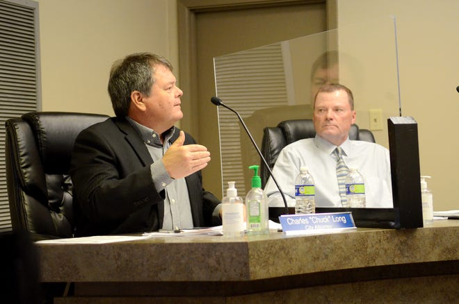 """Donaldsonville City Attorney Charles """"Chuck"""" Long speaks as council member Michael Sullivan looks on during the April 27 council meeting."""