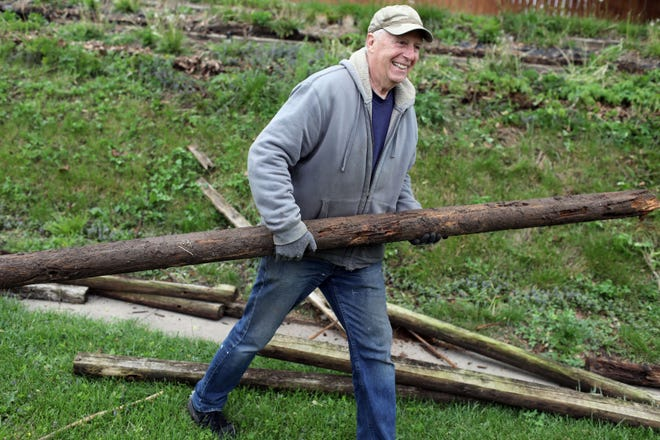 Jerry Parks, a retired educator and school administrator, removes landscaping timbers from a resident's yard Tuesday in Burlington. The work is part of Parks' ongoing effort to beautify Burlington by volunteering his services to area residents cleaning yards and painting porches.