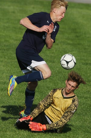 Notre Dame-West Burlington's Cole Ward (9) collides with goalkeeper Levi Svoboda (4) during the first half of their game against Danville-New London High School Tuesday May 4, 2021, at Notre Dame High School.