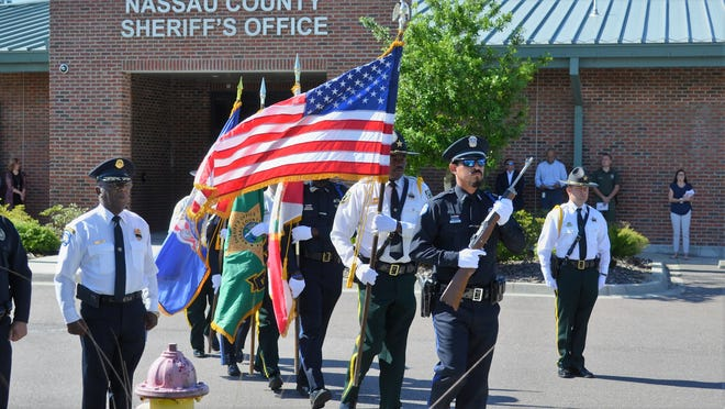 An honor guard made up of Nassau County deputies and Fernandina Beach police officers brings the American flag and others into a memorial for fallen officers.