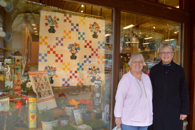 Colleen Dekker, left, and Cheryl Zylman, right, pose for a photo with the quilt they designed and made for this year's Tulip Time Quilt Raffle. The quilt is on display in the window of Apothecary Gift Shop, 35 W. Eighth St., Holland.