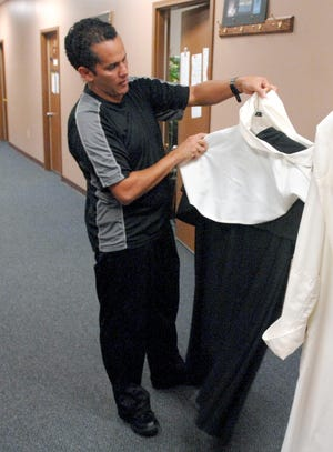 """In this 2013 file photo, Peoria Ballet artistic director Servy Gallardo looks over costumes for """"The Changeless Mover Ballet."""""""
