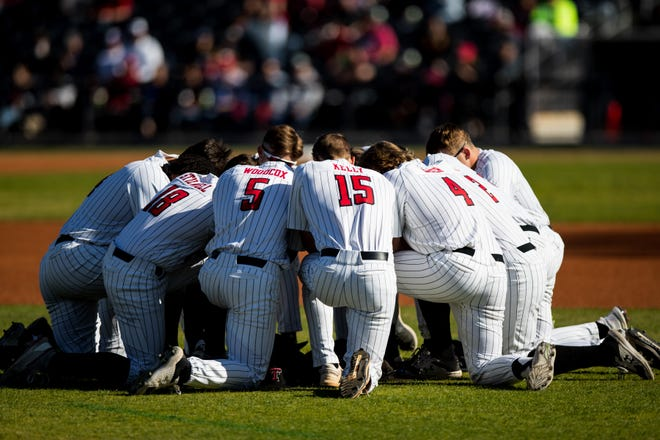 Texas Tech players pray before a neutral-site, nonconference Red Dirt Rivalry game May 4 against Oklahoma at HODGETOWN Stadium in Amarillo. The two teams play again in Big 12 Conference action starting with a 6:30 p.m. Friday contest in Norman, Oklahoma.