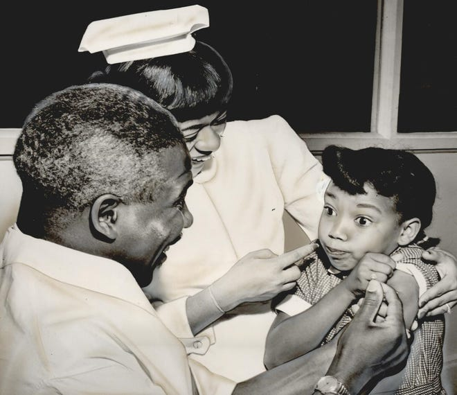 """Dunbar School student Theresa Ann Scruggs receives encouragement as she gets a polio vaccine in May 1954. Dr. G.E Finley administered the shot as part of a trial to vaccinate students across Oklahoma County. Crooked Oak School children became the first of the """"polio pioneers"""" to receive the three-shot vaccine. After some county students missed their second shot, health officials reminded parents of the necessity to receive all three shots for effective antibody production. This photo was published May 6, 1954, in the Oklahoma City Times."""