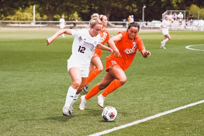 Oklahoma State midfielder Kim Rodriguez (26) fights for possession with Texas A&M forward Ali Russell (12) last Wednesday in the NCAA women's soccer tournament regional semifinals in Cary, N.C. The Aggies won 4-3 on penalty kicks.