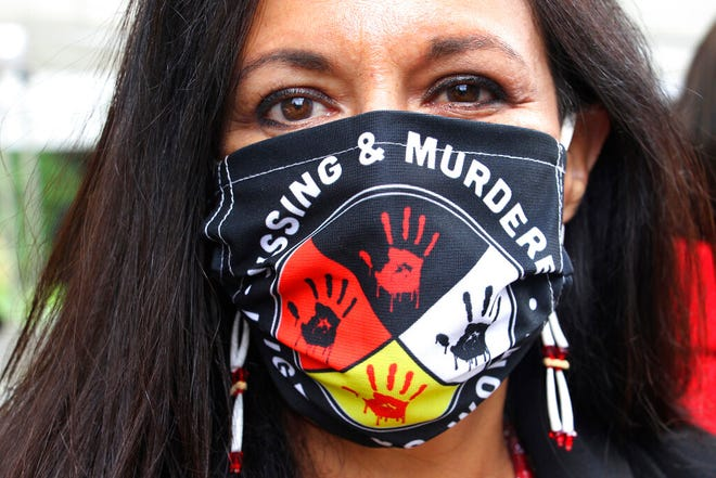 In this Aug. 26 photo, Jeannie Hovland, the deputy assistant secretary for Native American Affairs for the U.S. Department of Health and Human Services, poses with a Missing and Murdered Indigenous Women mask, in Anchorage, Alaska, while attending the opening of a Lady Justice Task Force cold case office in Anchorage, which will investigate missing and murdered Indigenous women. From the nation's capital to Indigenous communities across the American Southwest, top government officials, family members and advocates are gathering Wednesday as part of a call to action to address the ongoing problem of violence against Indigenous women and children.