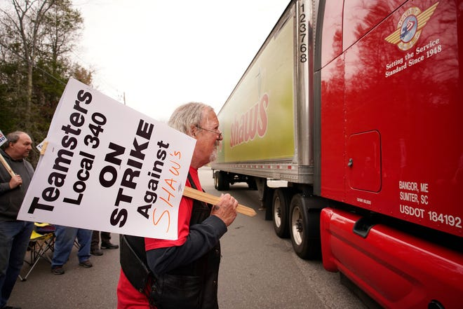 Jim Kelly, a truck driver with Shaw's supermarkets, looks at the driver of a truck leaving a Shaw's distribution facility while walking a picket line on strike, Monday, May 3, 2021, in Wells, Maine.