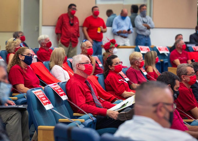 Residents of Legend Lake Estates, who are strongly opposed to the Amber Woods and Legend Lakes Center projects proposed for unincorporated Lake Worth, wear red shirts in opposition as county commissioners consider the projects Wednesday, May 5, 2021.