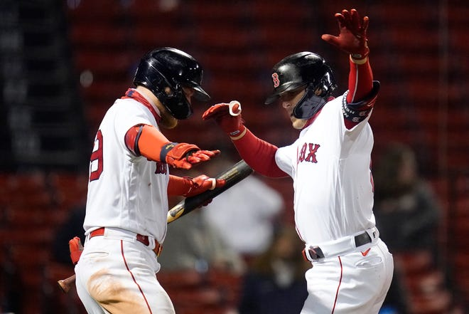Boston Kiké Hernandez, right, dances with Alex Verdugo as he crosses the plate after his solo home run against the Detroit Tigers in the eighth inning Tuesday night  at Fenway Park.