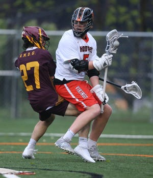 Drew Logan of Hoover takes a hit from Bill Holtzer of Walsh Jesuit at Hoover.