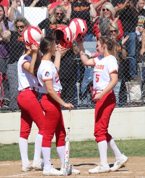 Sam Hartman (right) is congratulated by some of her teammates at home plate after hitting one of her four home runs Wednesday against Valliant in the first round of the Class 4A State Slow Pitch Tournament at the Ballfields at Firelake.