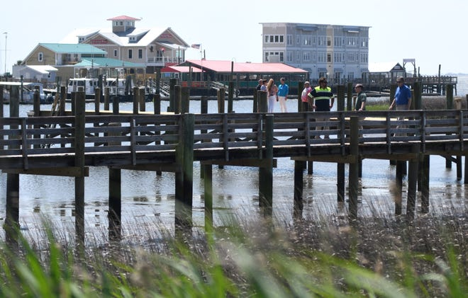 People walk on the newly reopened Southport City Dock following a ribbon cutting in downtown Southport, N.C., Wednesday, May 5, 2021. The dock was originally built in 1964 but had been closed since 2016 due to damage from Hurricane Matthew. The dock also received damage from Hurricane Florence in 2018 and Hurricane Isaias in 2020.