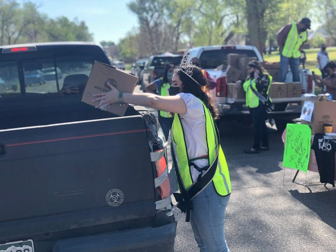Martha Esparza, the 2020 Fiesta Queen, drops a box of food into the bed of a truck at the 2021 Cinco de Mayo event at Plaza Verde Park. The event featured a food distribution and COVID-19 vaccination clinic