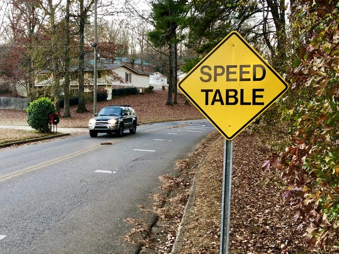 A motorist heads out of the Woodland Hills neighborhood after crossing a speed table on Woodland Road in 2018.